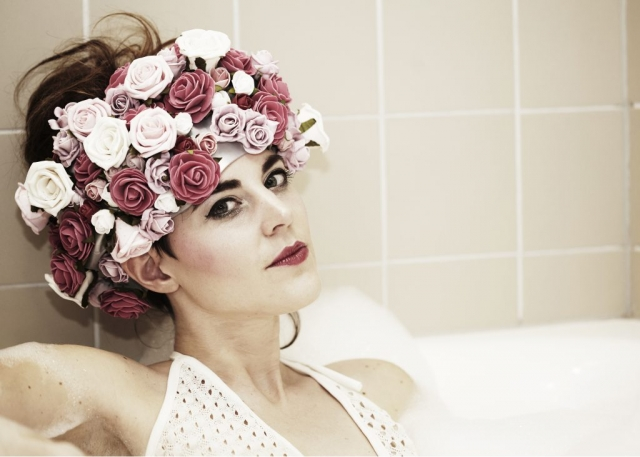 Model in bath with roses on her head